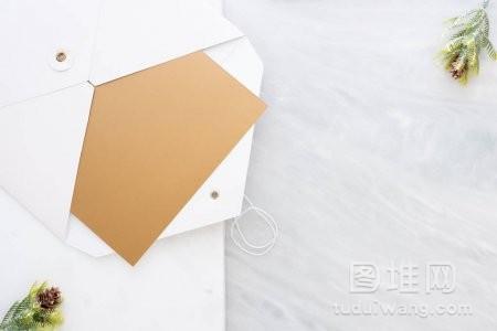 在大理石桌面的两层台阶上用松叶在白色信封