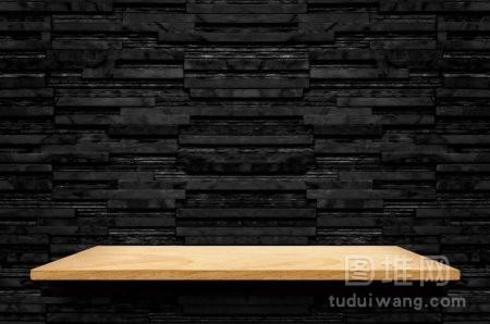 空木架子在黑层大理石瓦片墙壁背景模仿